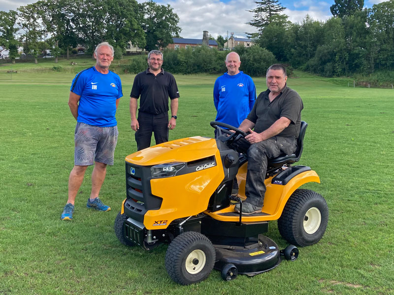 A photo of members of the Sports Club with the new mower.